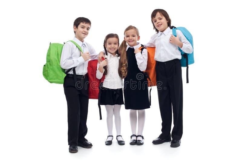 Szczęśliwi szkoła podstawowa dzieciaki z kolorowymi tylnymi paczkami obraz royalty free