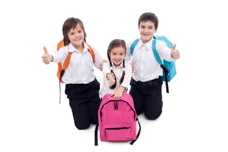 Szczęśliwi szkolni dzieciaki daje aprobata znakowi obrazy royalty free