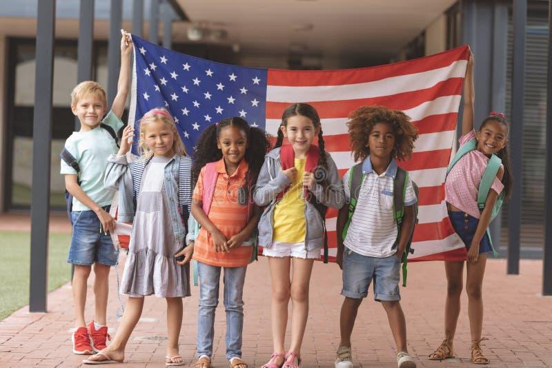 Szczęśliwi szkolni ucznie stoi w korytarzu podczas gdy trzymający flagę amerykańską obraz stock