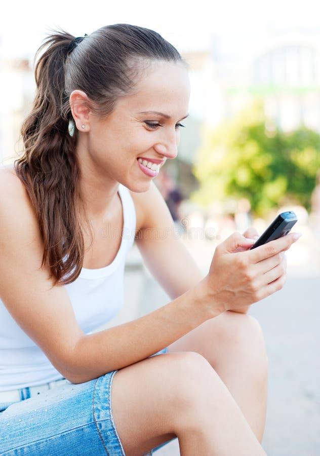 szczęśliwi telefon komórkowy kobiety potomstwa zdjęcie royalty free
