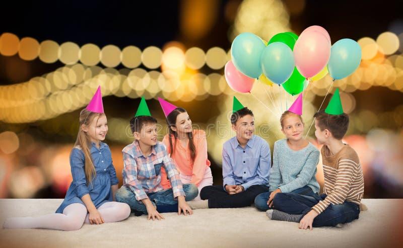 Szczęśliwi uśmiechnięci dzieci w partyjnych kapeluszach przy urodziny obraz stock