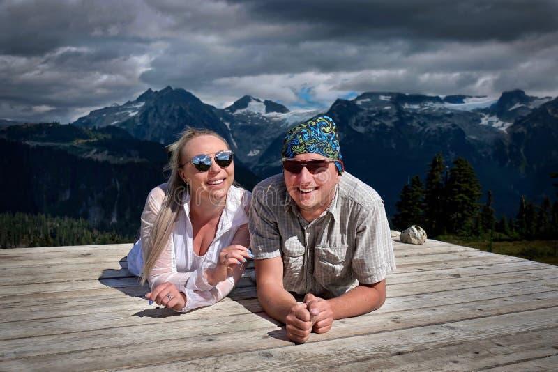 Szczęśliwi uśmiechnięci ludzie obozuje w górach Para małżeńska na namiotowym ochraniaczu ma zabawę i relaksować fotografia royalty free