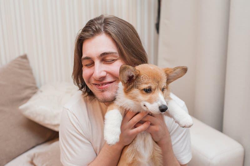 Szczęśliwi uśmiechnięci mężczyzna cuddles z szczeniaka Corgi obraz stock