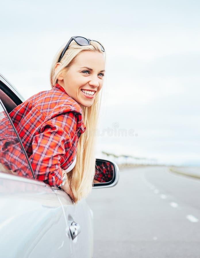 Szczęśliwi uśmiechnięci młodych kobiet spojrzenia out od samochodowego okno obrazy stock