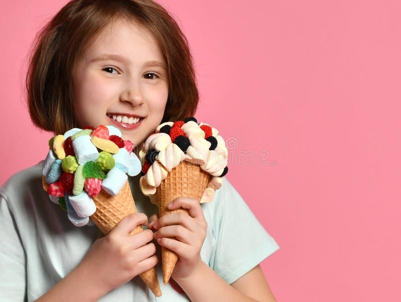 Szczęśliwi uśmiechnięci nastoletni dziewczyna dzieciaka chwyty bliżej do ona twarzy dwa duży lody w gofrach konusują z polewami w obrazy stock