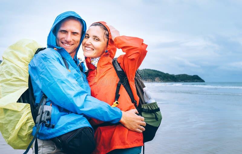 Szczęśliwi uśmiechnięci podróżnicy dobierają się w deszczowym dniu na ocean plaży obraz stock