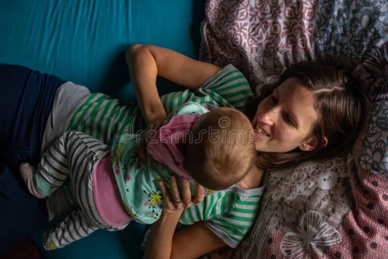 Szczęśliwi uśmiechnięci potomstwa matkują lying on the beach na łóżku bawić się z jej dzieckiem obrazy royalty free