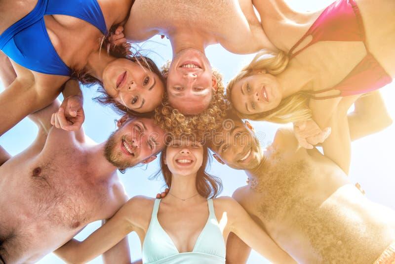 Szczęśliwi uśmiechnięci przyjaciele przy pogodną plażą obrazy royalty free