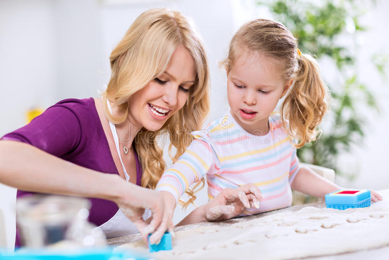 Szczęśliwi uśmiechnięci rodzinni kształtujący ciastka fotografia stock