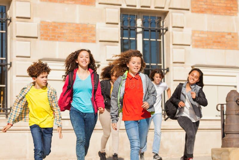 Szczęśliwi ucznie biega outdoors z plecakami obrazy royalty free