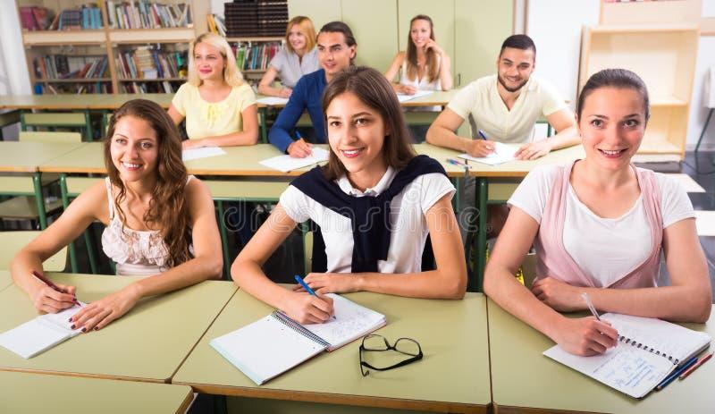 Szczęśliwi ucznie pisze tescie indoors zdjęcie royalty free
