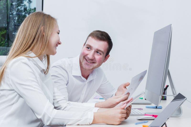 Szczęśliwi urzędnicy siedzi w biurze patrzeje each inny fotografia royalty free