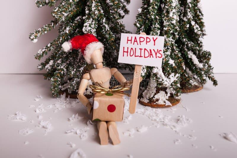 Szczęśliwi wakacje palikują znaka trzymającego drewnianą spajającą manikin lalą z zawijającym prezentem jest ubranym Święty Mikoł zdjęcie royalty free