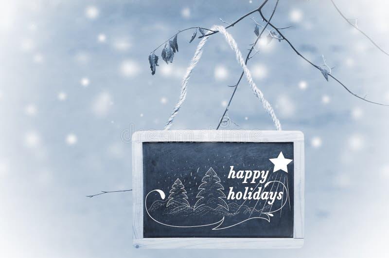 Szczęśliwi wakacje pisać na czarnym kredowej deski obwieszeniu od drzewa na błękitnym, śnieżnym tle, cukierku trzciny bożych naro zdjęcia royalty free
