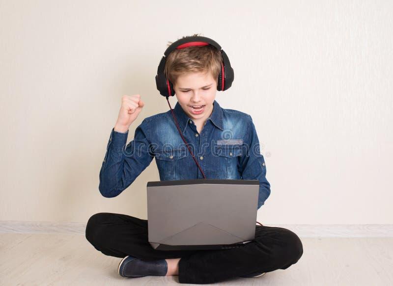 Szczęśliwie wygrywający nastolatek, pracujący lub bawiący się na komputerze przenośnym, siedzący na podłodze z nogami skrzyżowany fotografia royalty free