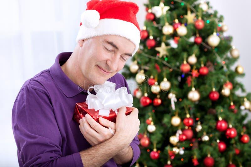 Szczęśliwy śliczny starszy mężczyzna ściska jego prezent dla bożych narodzeń fotografia royalty free