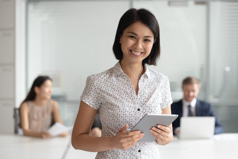 Szczęśliwy żeński azjatykci kierownik patrzeje kamerę trzyma cyfrową pastylkę obrazy royalty free