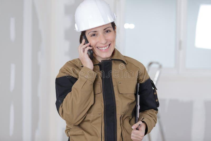 Szczęśliwy żeński budowa organizator na telefonie z męskimi pracownikami zdjęcia stock