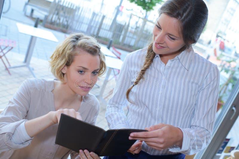 Szczęśliwy żeński kelnera writing rozkazu blondynki klient zdjęcia royalty free