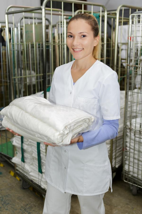 Szczęśliwy żeński pralniany pracownik przy suchymi czyścicielami fotografia stock