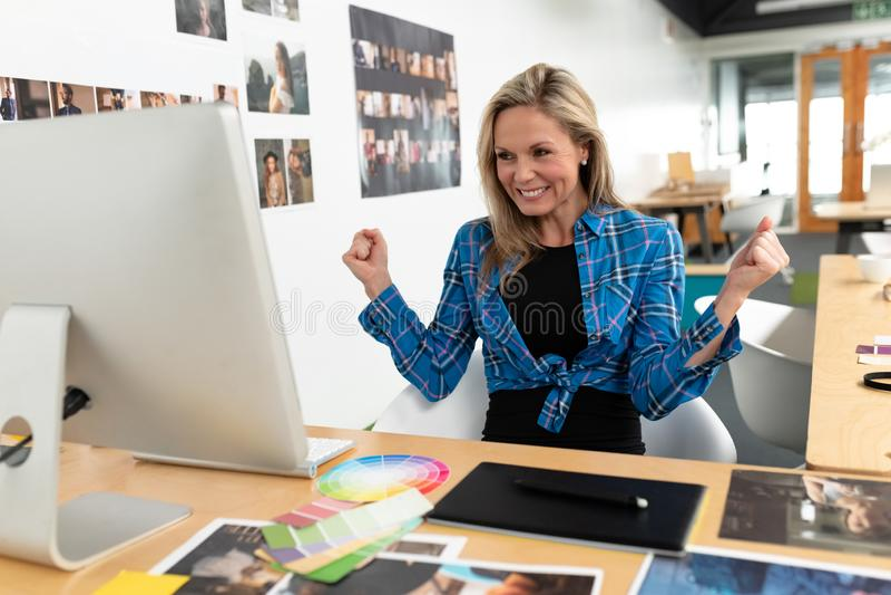 Szczęśliwy żeński projektant grafik komputerowych odświętności sukces przy biurkiem zdjęcia stock
