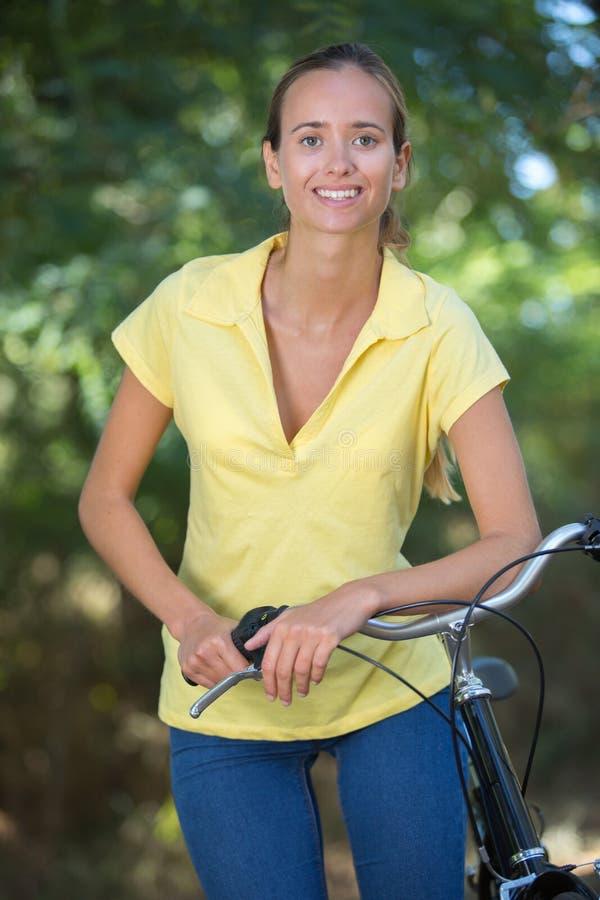 Szczęśliwy żeński rowerzysta na polu w lesie obrazy royalty free