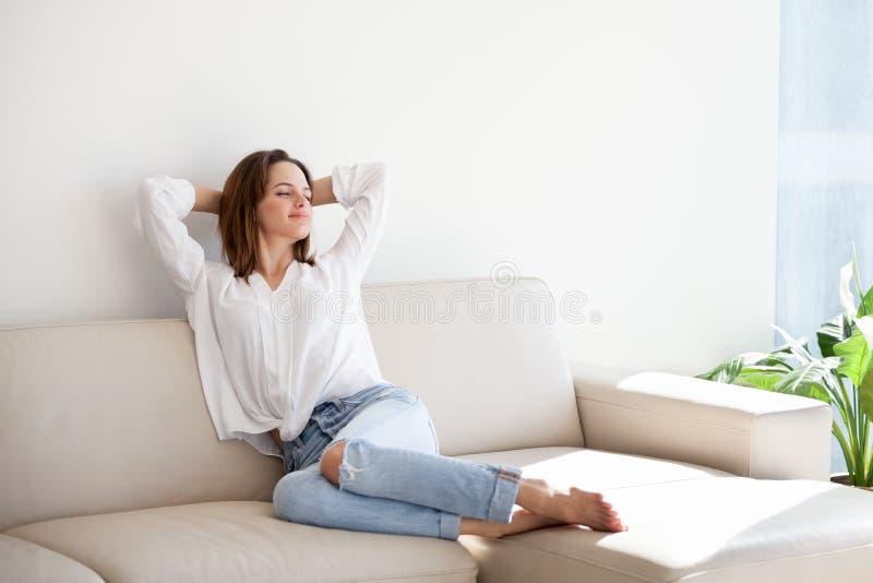 Szczęśliwy żeński rozciąganie na wygodnym powozowym wydatki weekendzie w domu zdjęcia royalty free