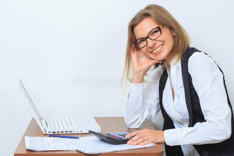 Szczęśliwy żeński urzędnik siedzi przy jej biurkiem i fotografia stock
