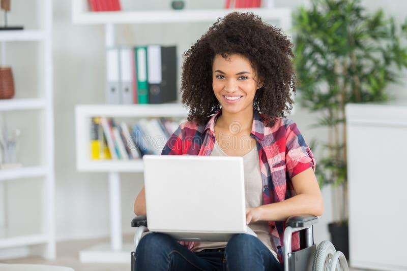 Szczęśliwy żeński urzędnik w wózka inwalidzkiego mienia laptopie zdjęcie royalty free