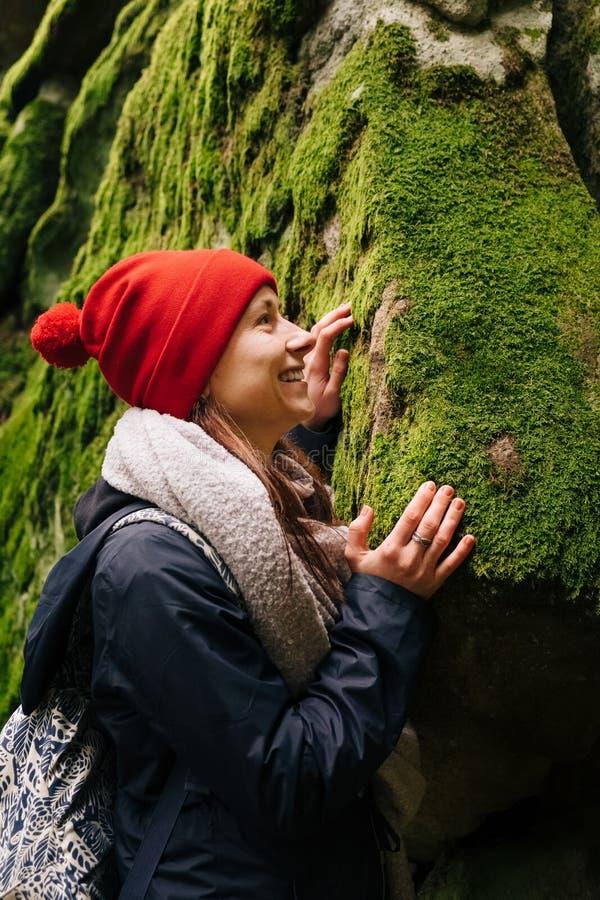 Szczęśliwy żeński wycieczkowicza macania zieleni mech w lesie obrazy royalty free