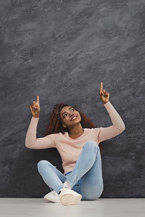 Szczęśliwy afrykański dziewczyny obsiadanie na podłoga i wskazywać up palcach zdjęcie stock