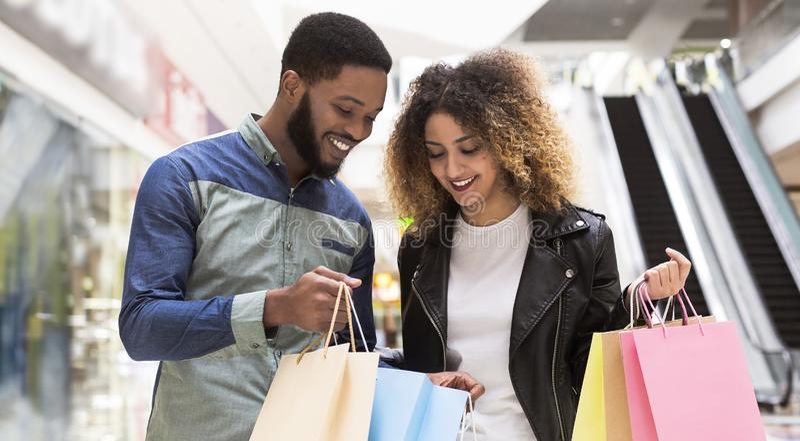 Szczęśliwy afrykański mężczyzna pokazuje jego dziewczyna zakupy fotografia royalty free