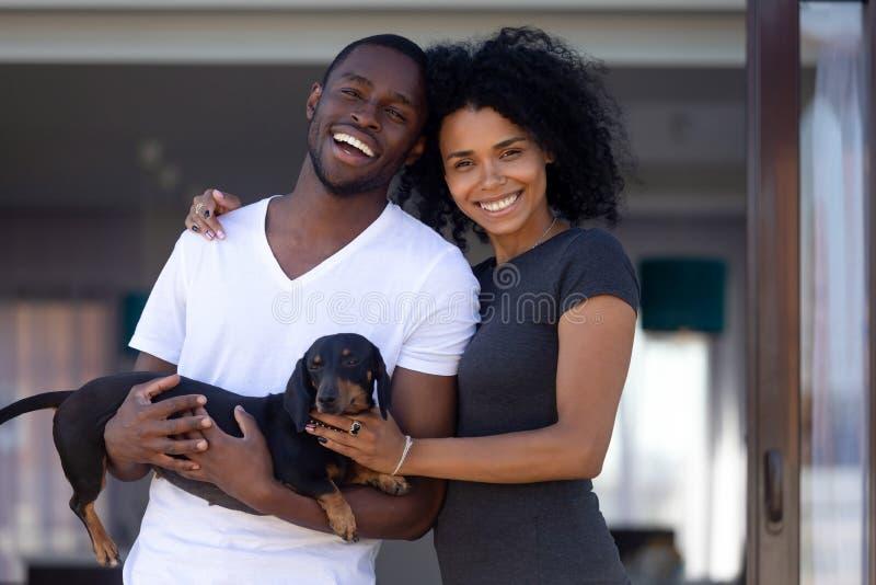 Szczęśliwy afrykański millennial para uścisk outdoors trzyma zwierzęcia domowego, portret zdjęcia stock