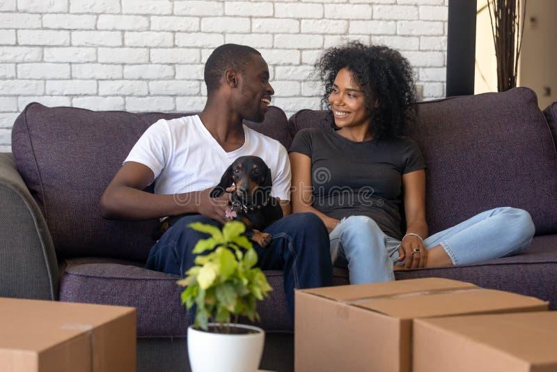Szczęśliwy afrykański pary chodzenie w nowego dom z zwierzęciem domowym boksuje zdjęcia royalty free