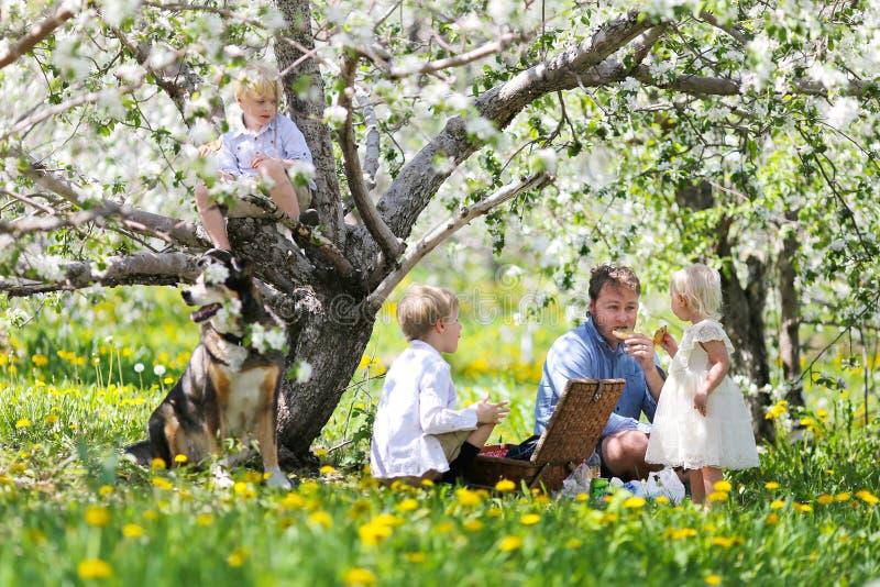Szczęśliwy Amerykański rodziny i psa łasowania Pykniczny lunch Pod Flowerin obrazy stock