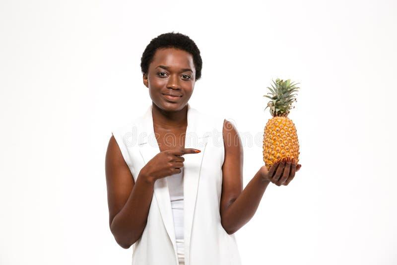 Szczęśliwy amerykanin afrykańskiego pochodzenia kobiety mienia ananas i wskazywać na nim zdjęcie stock