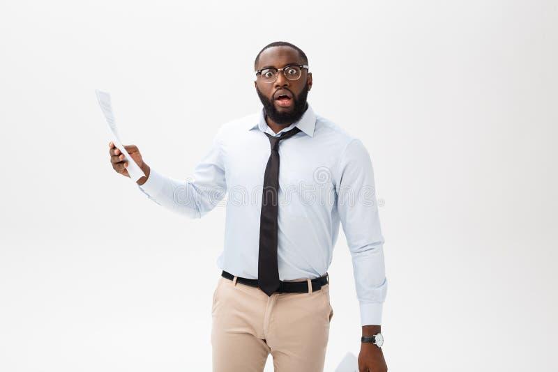 Szczęśliwy amerykanin afrykańskiego pochodzenia mężczyzna trzyma documaent papier nad odosobnionym białym tłem z niespodzianki i  zdjęcia royalty free
