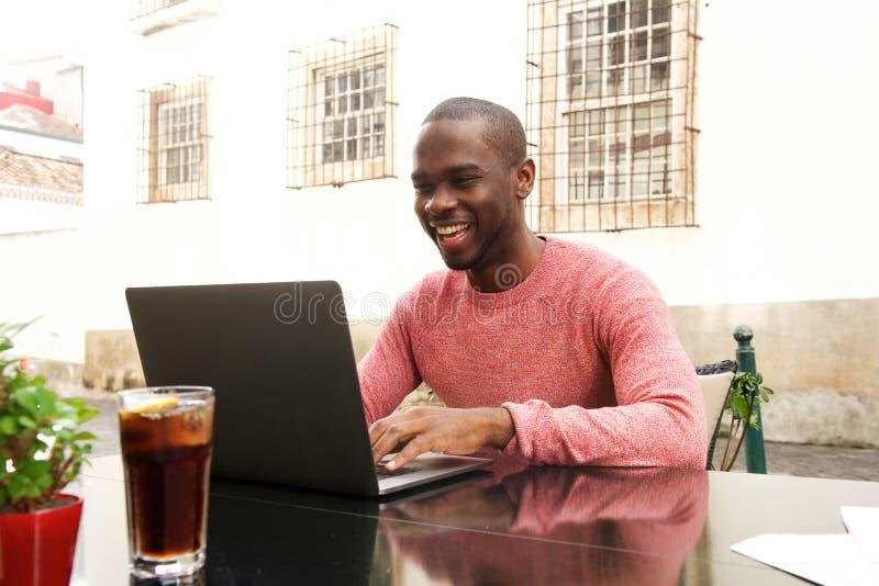 Szczęśliwy amerykanin afrykańskiego pochodzenia mężczyzny obsiadanie przy cukiernianym działaniem z laptopem zdjęcia royalty free