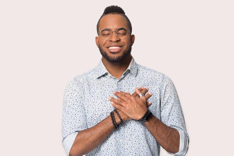 Szczęśliwy Amerykanin trzyma ręce w klatce piersiowej obrazy stock