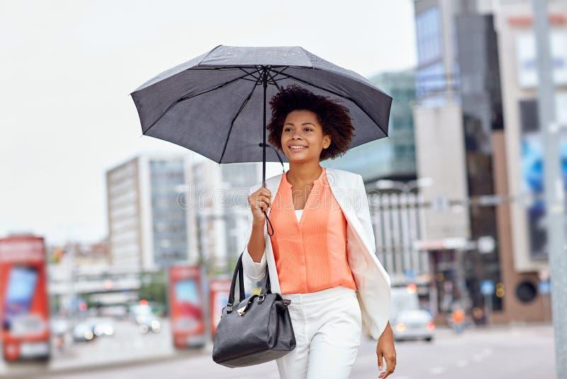 Szczęśliwy amerykanina afrykańskiego pochodzenia bizneswoman z parasolem obrazy royalty free