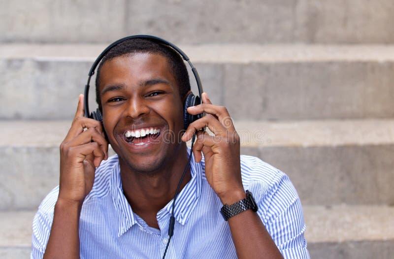 Szczęśliwy amerykanina afrykańskiego pochodzenia mężczyzna śmia się z hełmofonami zdjęcia stock
