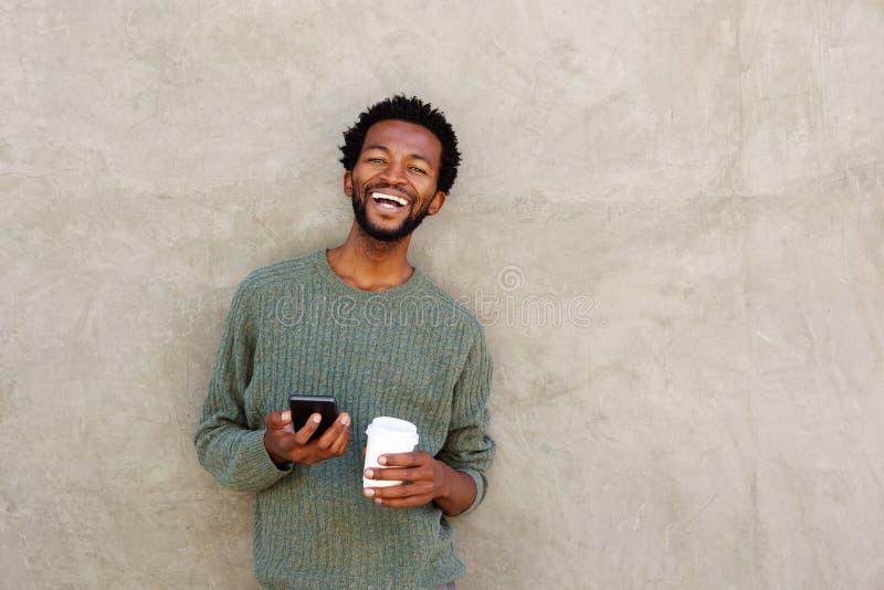 Szczęśliwy amerykanina afrykańskiego pochodzenia mężczyzna trzyma mądrze kawę i telefon fotografia stock
