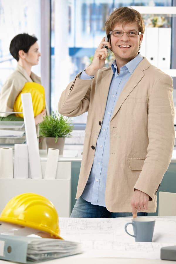Szczęśliwy architekt z hardhat przy biurem na telefonie fotografia royalty free