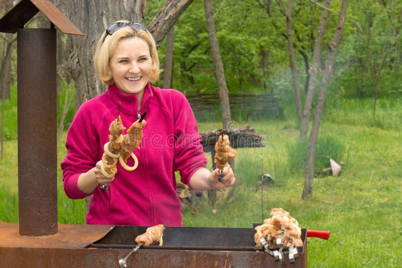 Szczęśliwy atrakcyjny blond kobiety kucharstwo na BBQ fotografia stock