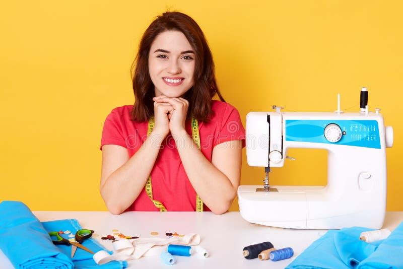 Szczęśliwy atrakcyjny młodej kobiety szwaczki obsiadanie przy pracującym stołem, utrzymań hads pod podbródkiem, patrzeje szczęśli obraz stock