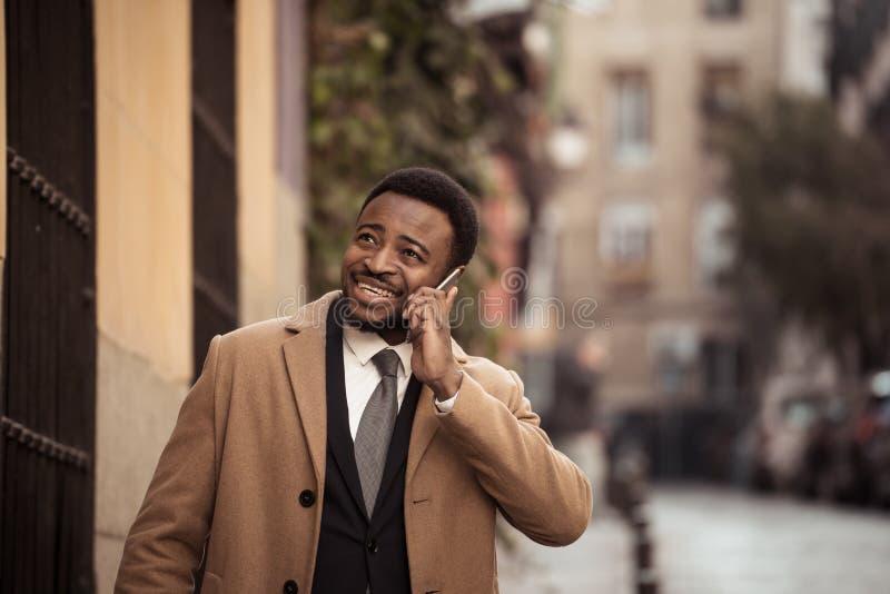 Szczęśliwy atrakcyjny młody biznesowy mężczyzna na jego mądrze telefonie podczas gdy chodzący w miasta ono uśmiecha się zdjęcie royalty free