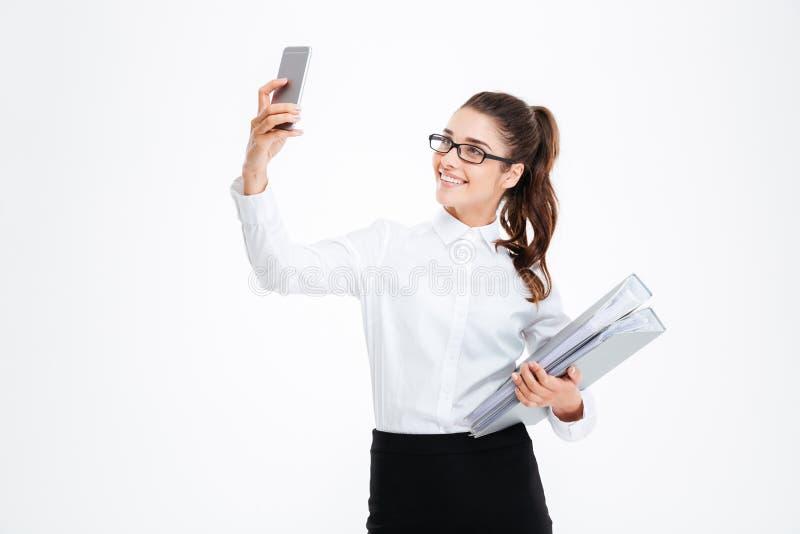 Szczęśliwy atrakcyjny młody bizneswoman w szkłach bierze selfie używać smartphone zdjęcia stock