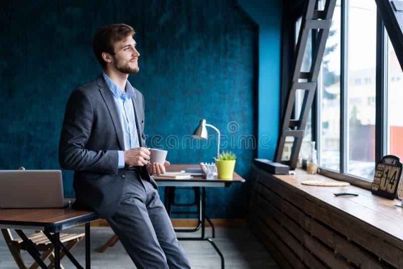 Szczęśliwy attracive młody biznesmen pije kawę w biurze zdjęcie stock