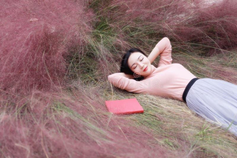 Szczęśliwy Azjatycki Chiński kobiety dziewczyny lying on the beach na trawa sen modli się kwiatu pola jesieni spadku parka gazonu fotografia stock