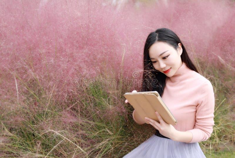 Szczęśliwy Azjatycki Chiński kobiety dziewczyny sztuki ipad telefon plenerowy siedzi na trawa gazonie w natury beztroskim selfie zdjęcie royalty free